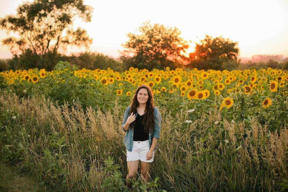 Cedar Falls senior photographers in field of sunflowers smiling in denim