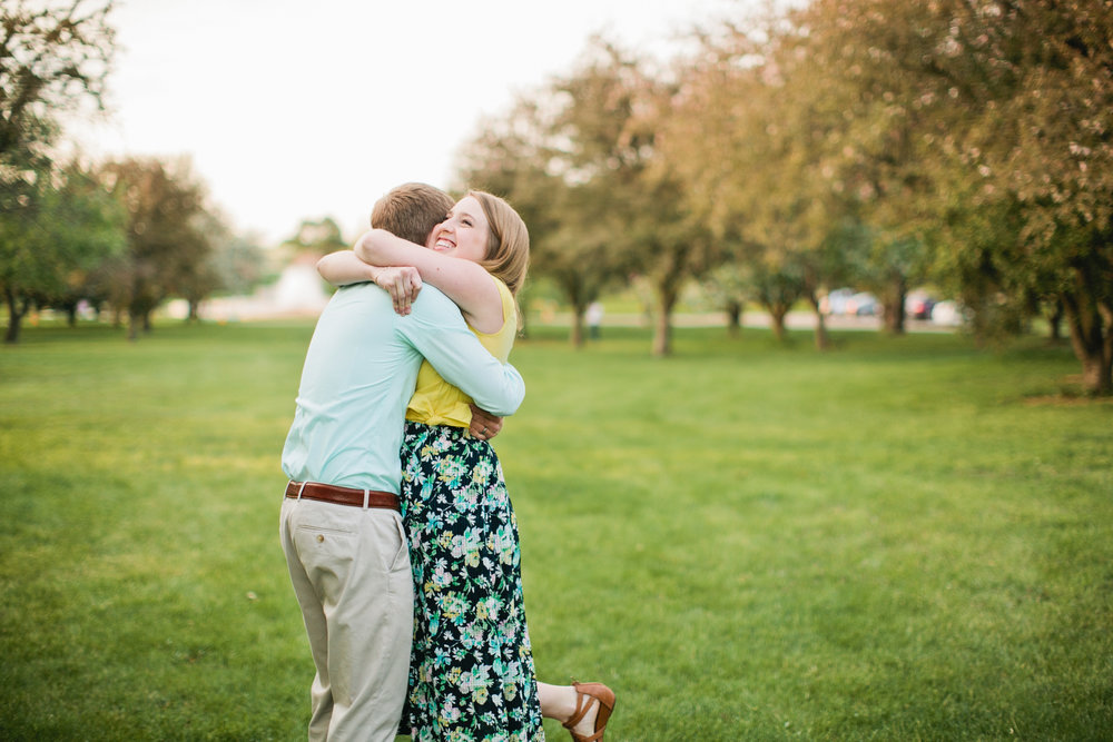 couple hugging in downtown park Des Moines wearing pastels