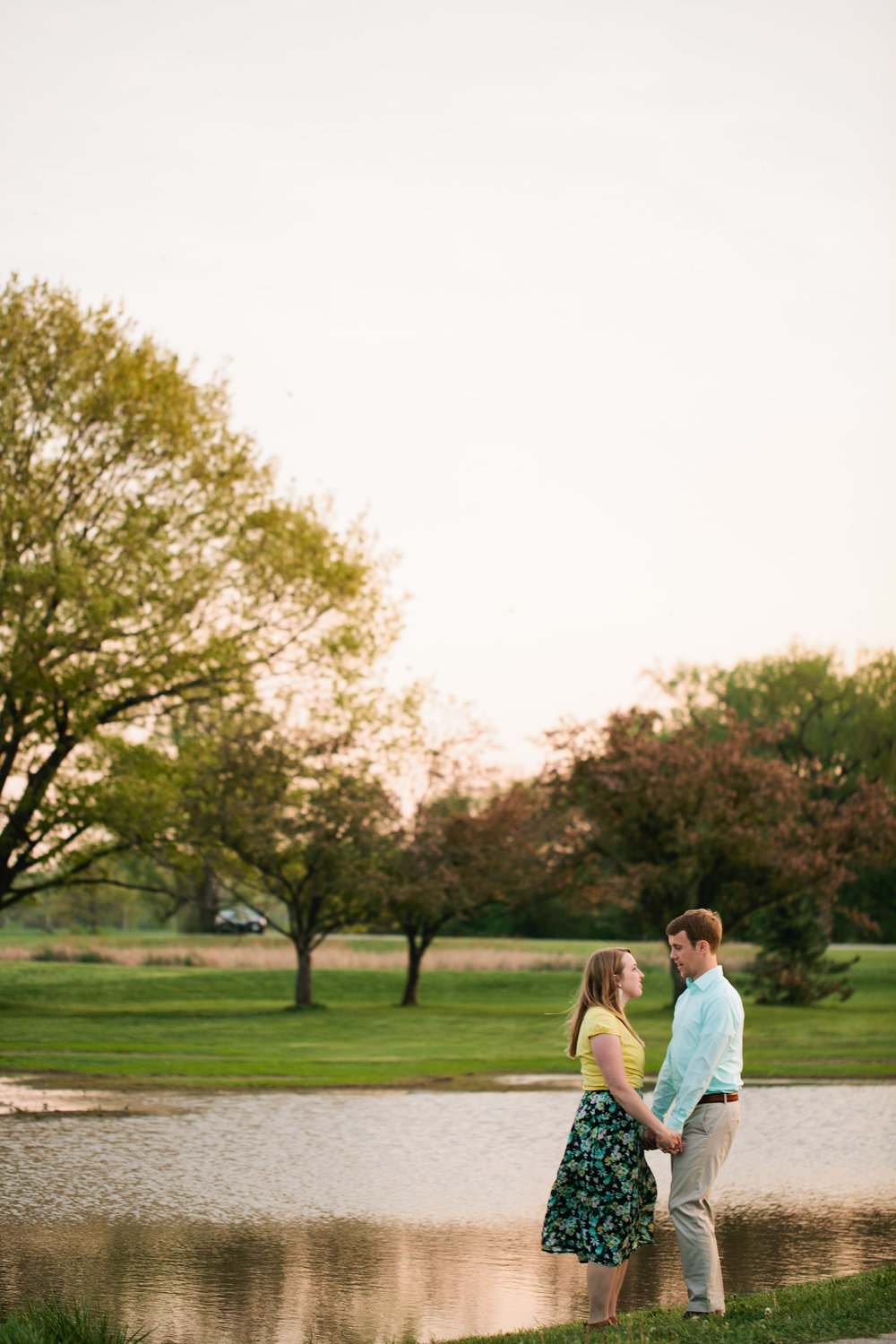boat engagement photos by tree and lake in Des Moines