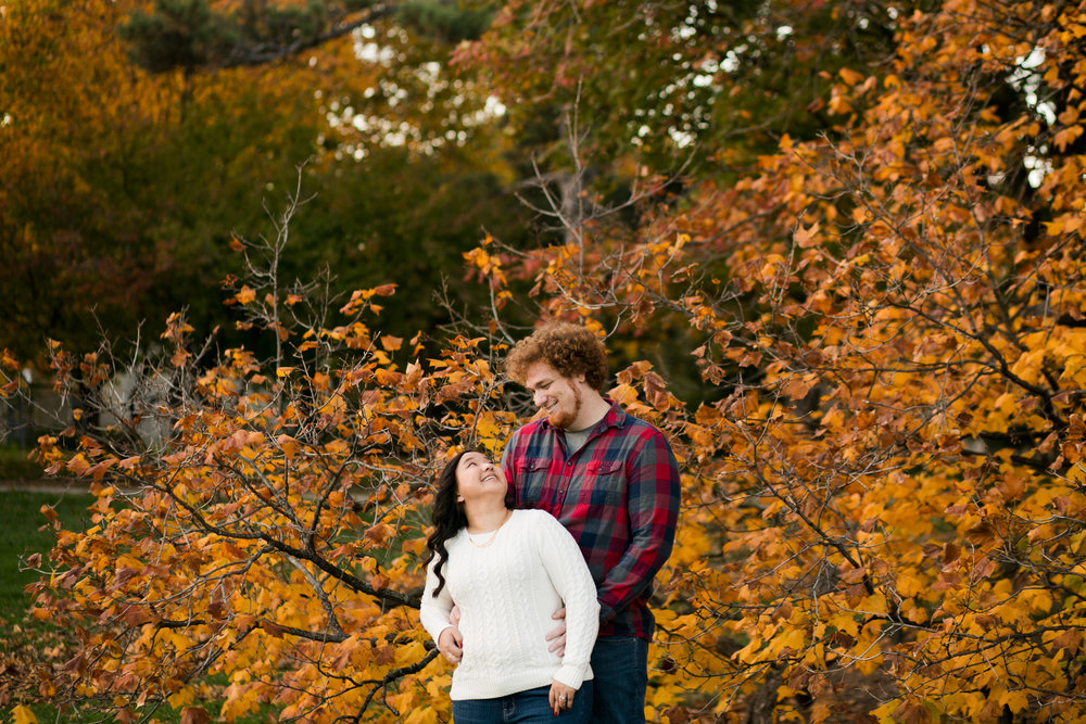 couple smiling at each other in front of fall leaves on trees in Des Moines