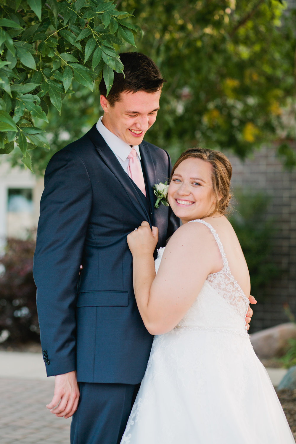 wedding photos of bride holding groom's lapel at noah's event center in des moines iowa