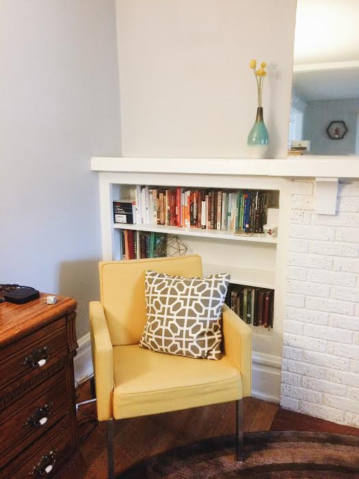 mid centruy modern yellow chair and built in white bookshelves