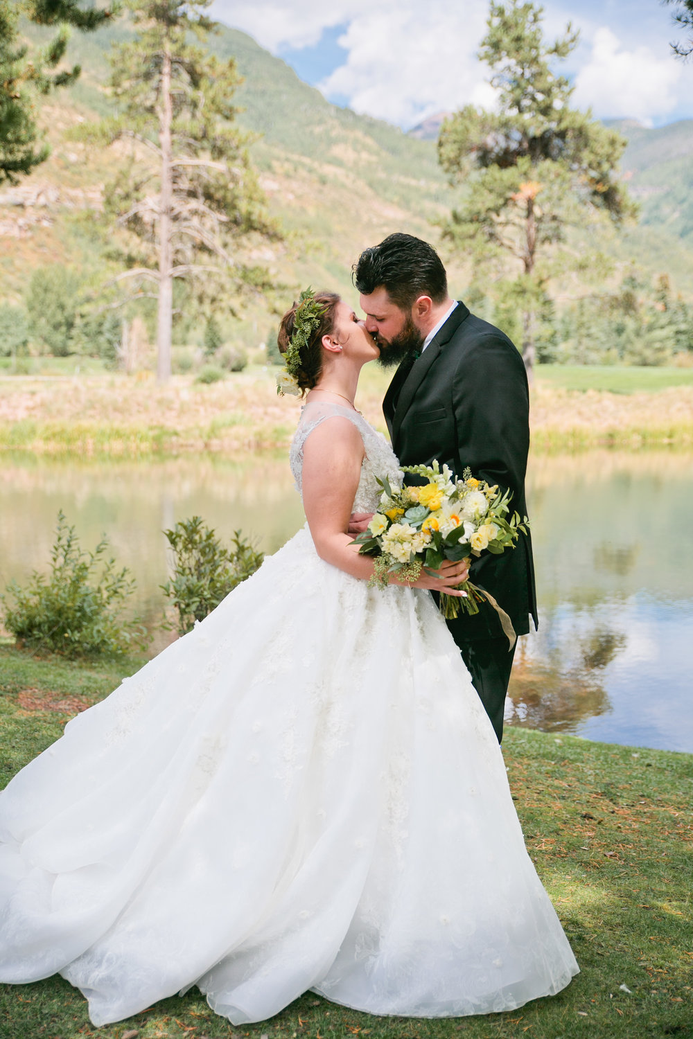 bride and groom kissing in front of mountains in Vail, Colorado during summer wedding