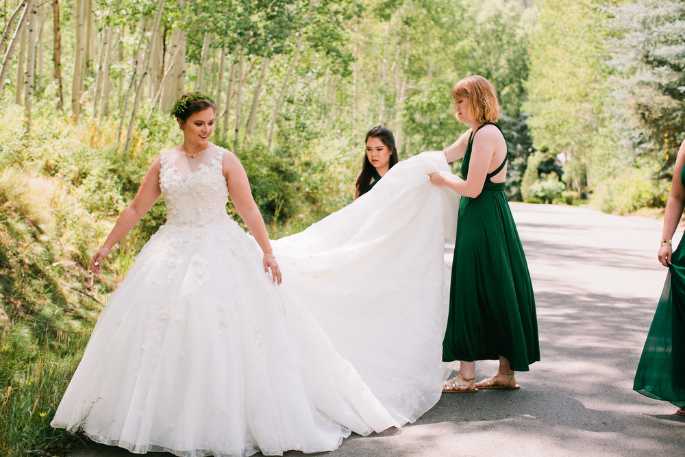 Bridesmaids in forest green dresses helping Colorado bride with her wedding dress train