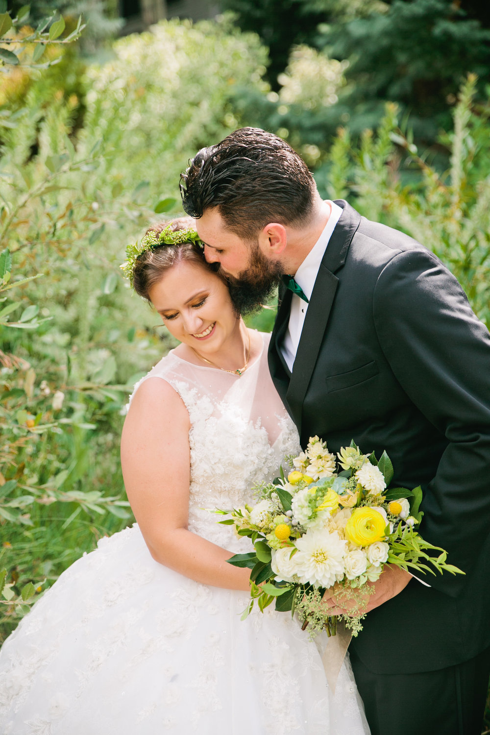 groom kissing bride in tall weeds with mountains in Vail Colorado