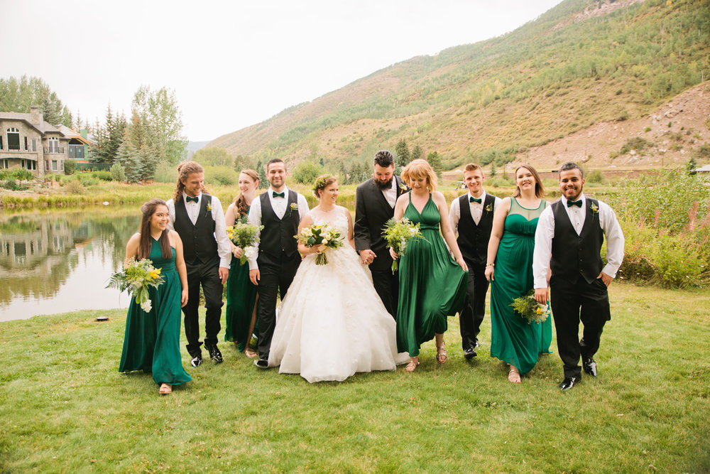 bridal party walking in green dresses and tuxedos outside in Vail for a Mountain wedding photography