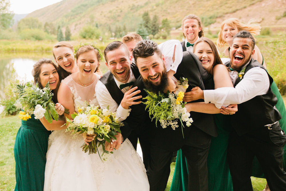 bridal party jumping on groom and bride, wearing green dresses and tuxedos outside in Vail for a Mountain wedding photography