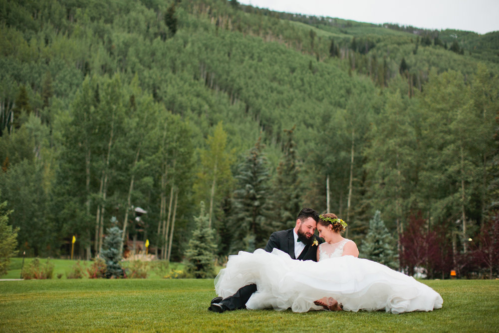 bride and groom sitting in the grass in the mountains during wedding reception