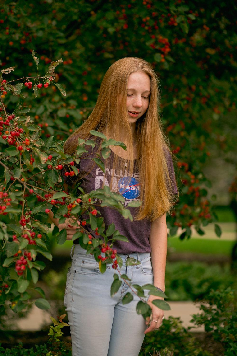 senior girl wearing nasa tshirt and light blue jeans standing in low tree