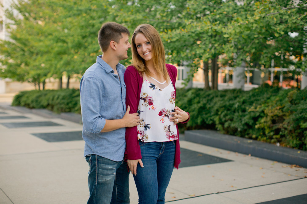downtown engagement photos with green trees and fall leaves // wearing blue jeans and sweaters