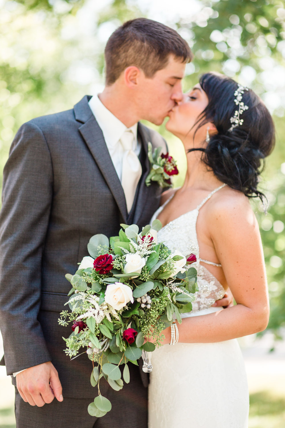 bride and groom kissing outside at Rollins Mansion Des Moines with flowers