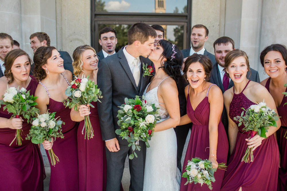 bridal party excited while bride groom kiss outside Iowa State Campus