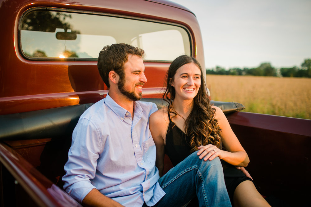 couple sitting in back of vintage red Ford pickup truck during engagement photos at sunset in Des Moines Iowa field laughing
