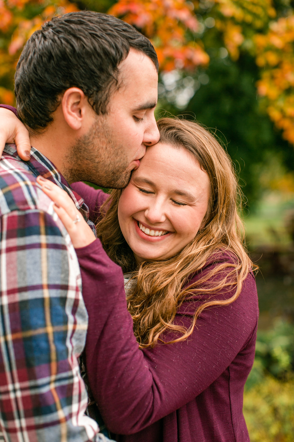 Fall engagement pictures in Des Moines University kissing on forehead