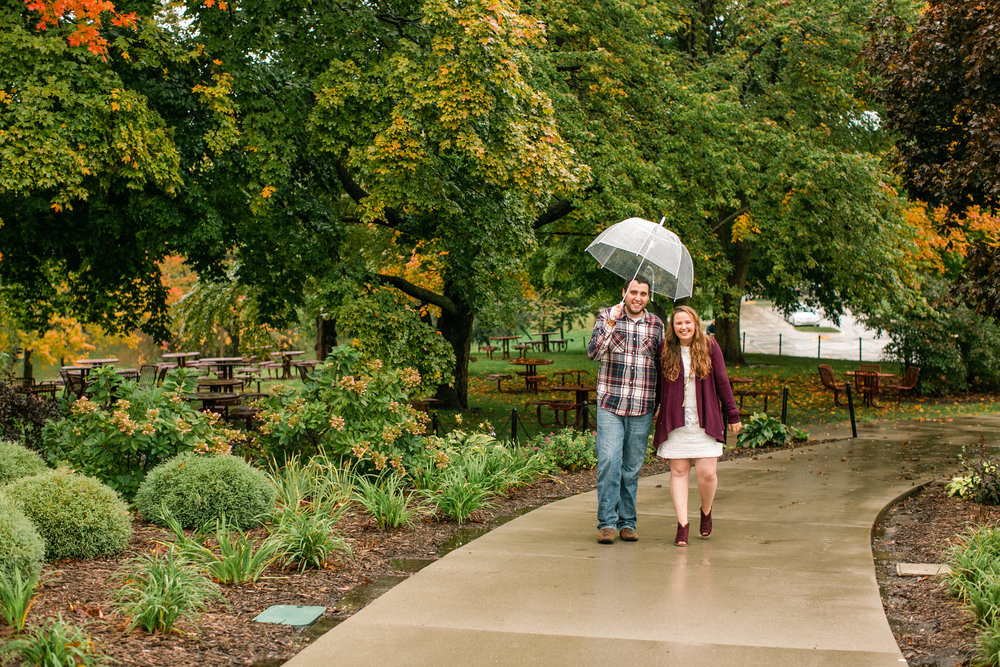 engaged couple walking on campus des moines university with umbrella in fall
