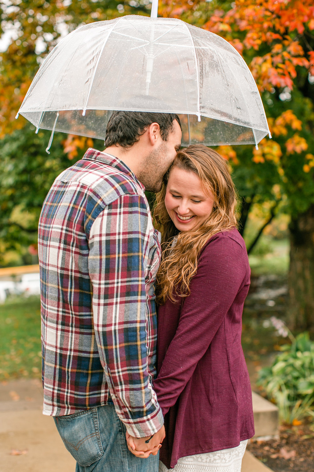 rainy fall engagement photos Des Moines University with umbrella what to wear for fall engagement photos