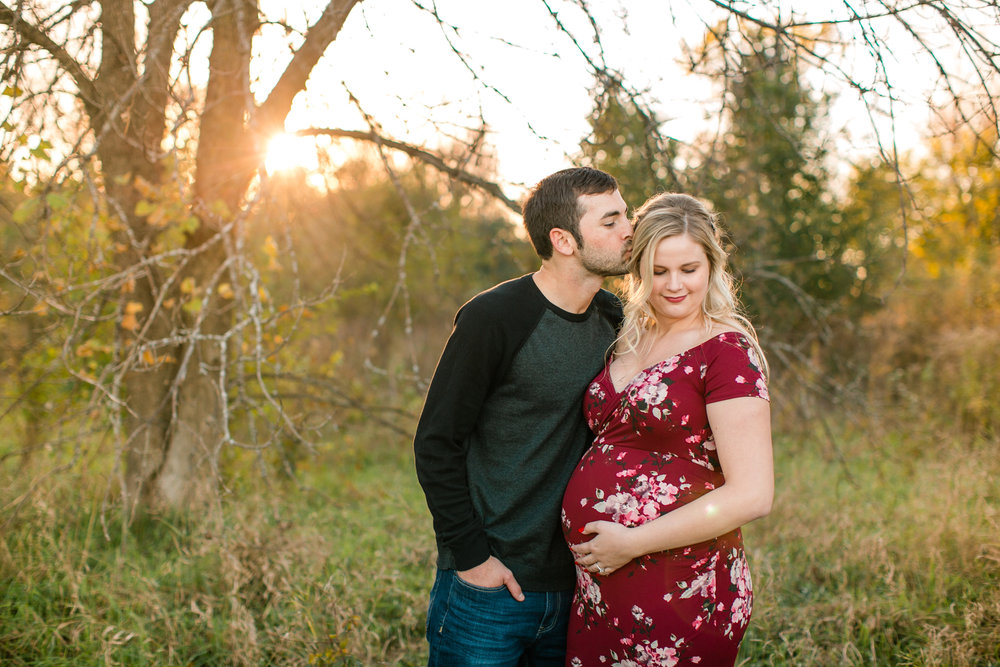 dad kissing mom at sunset outdoor maternity photos in red floral dress des moines iowa