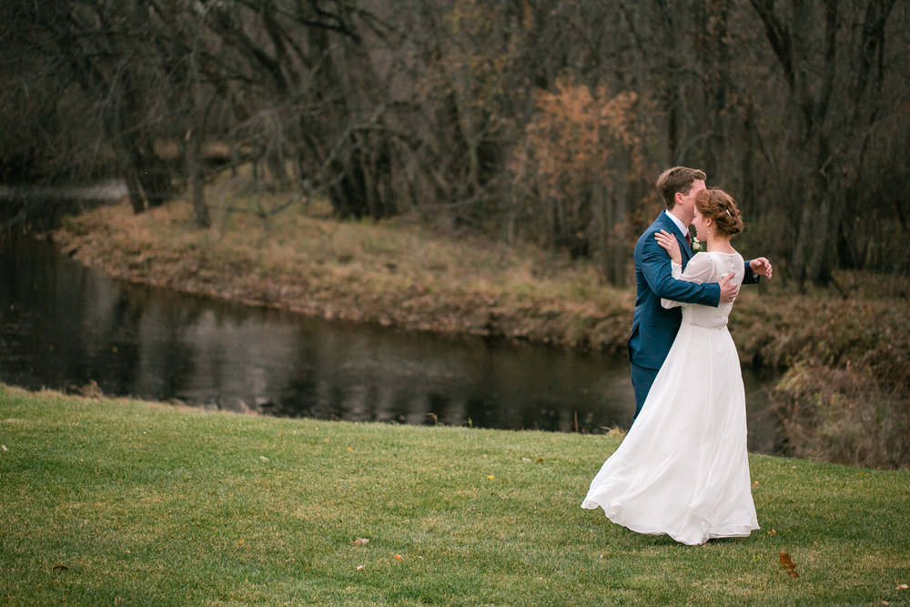 first look by river in October fall wedding wisconsin