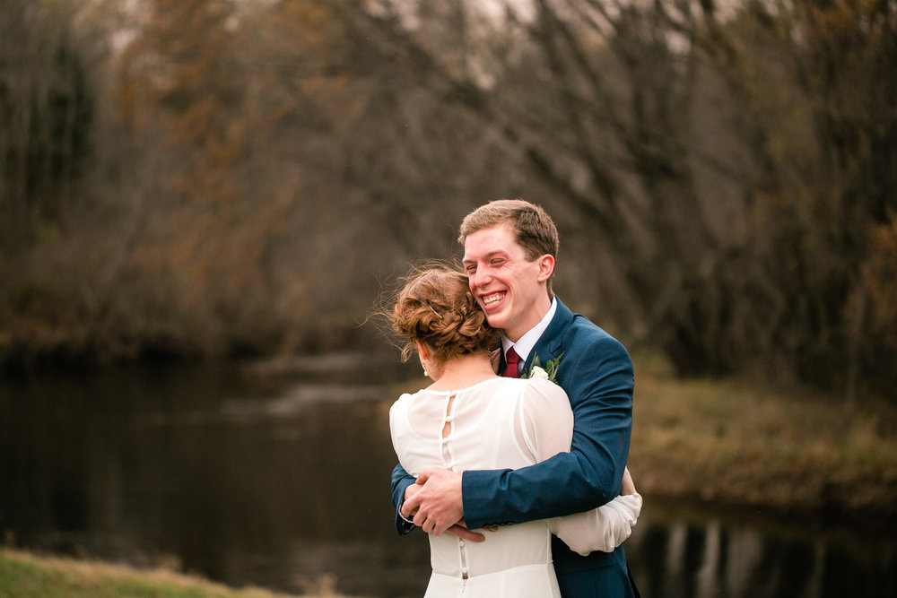 groom holding bride and beaming with joy smiling in outdoor wedding first look navy blue theme