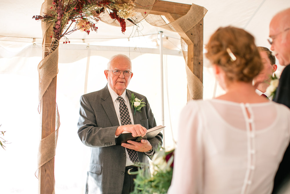 grandfather officiating wedding ceremony in tent intimate wedding photos