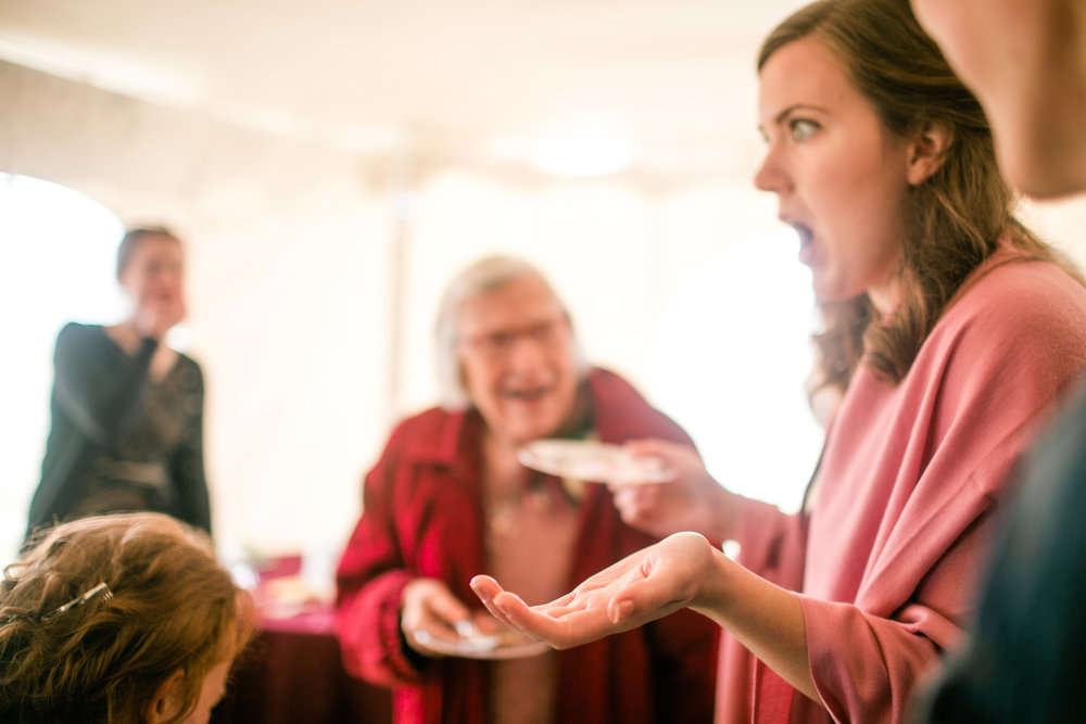 cousin telling bride story at wedding while grandma laughs candid wedding photography
