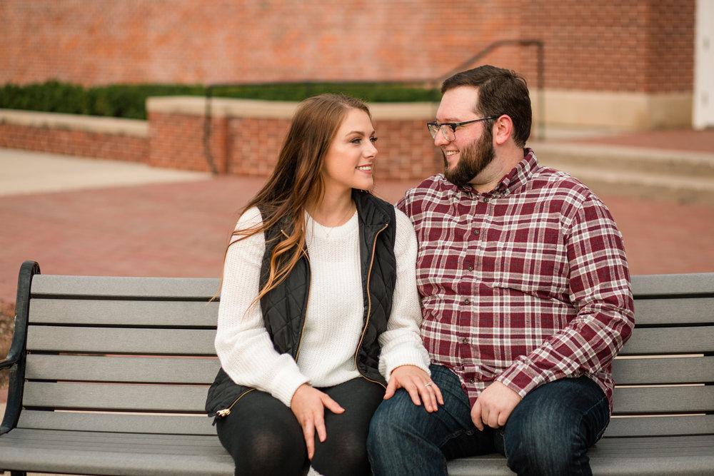 couple sitting on bench grimes urbandale ankeny wedding engagement photographers