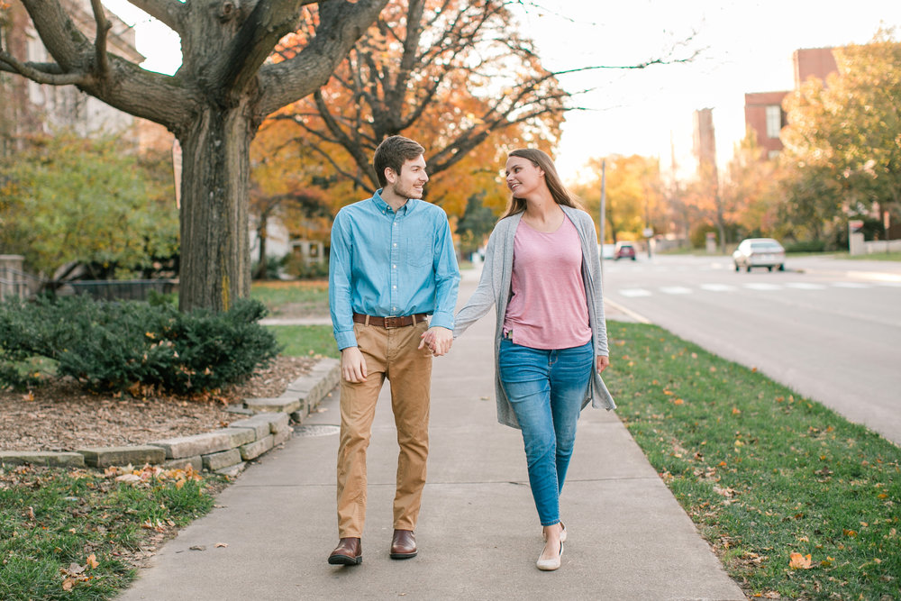 fiance walking down sidewalk at sunset engagement photos in Cedar Rapids