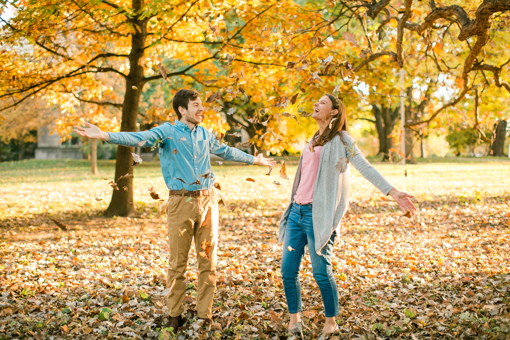 throwing leaves in fall engagement photos Iowa City Coralville wedding photographers and parks