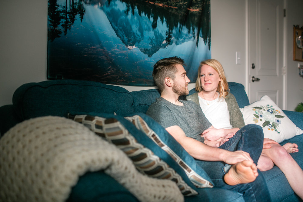couple sitting on blue couch in apartment photos