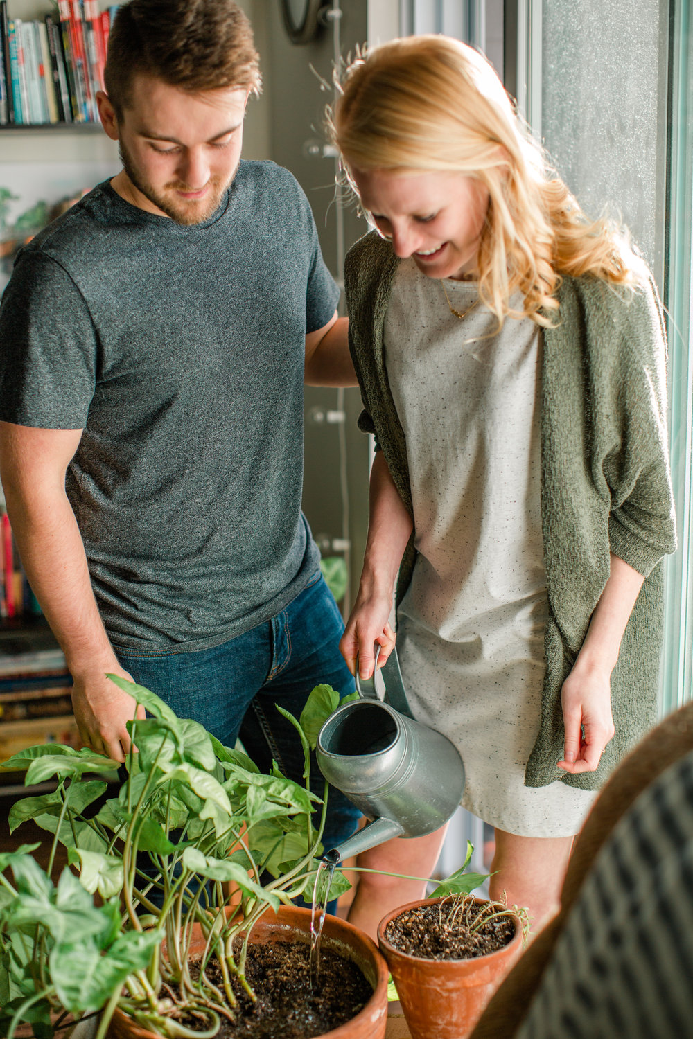 cute couple watering plants in apartment during anniversary photos