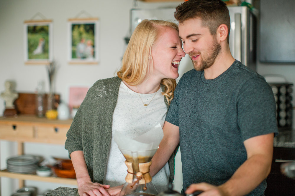 intimate moment couple laughing over coffee in their home