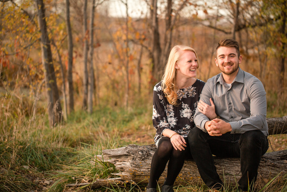 cute couple laughing and sitting on log in woods cozy engagement photos des moines iowa