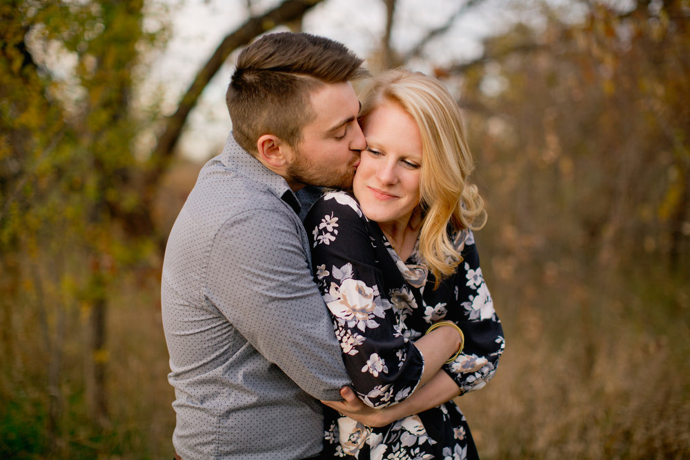 husband hugging wife and kissing her cheek outside des moines west engagement photos iowa des moines wedding photographers