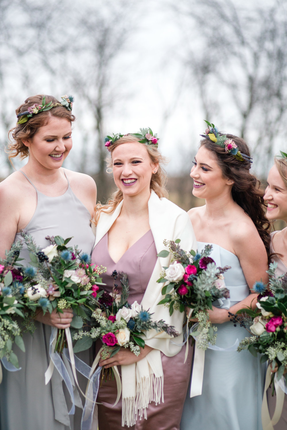 bride and bridesmaids giggling together holding wild boho flowers with cream ribbon