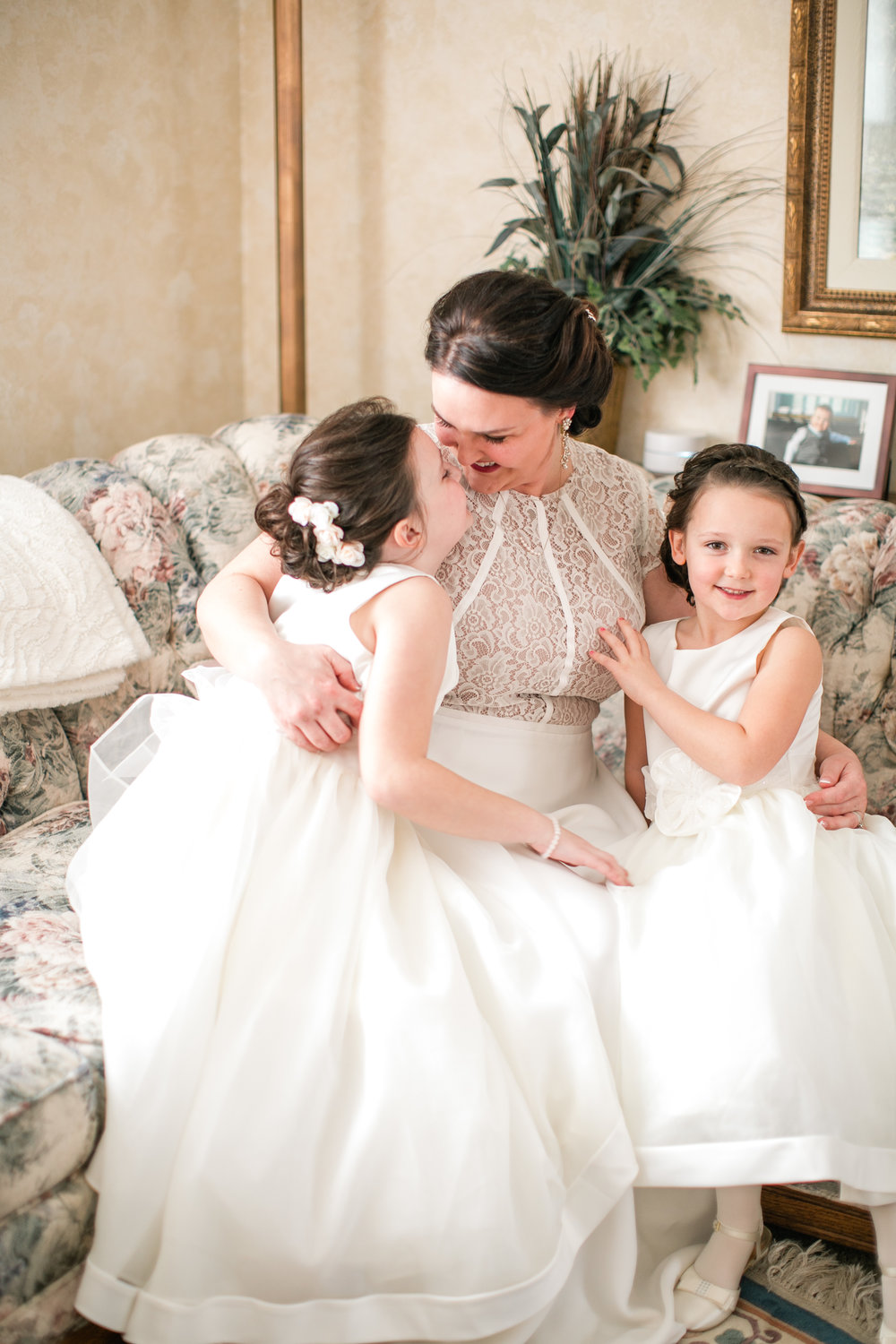 bride with her two daughters kissing in white dresses on couch wedding day des moines