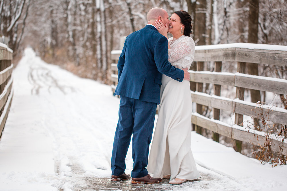 couple kissing first look winter snowy bridge Iowa in Des Moines wedding photographer
