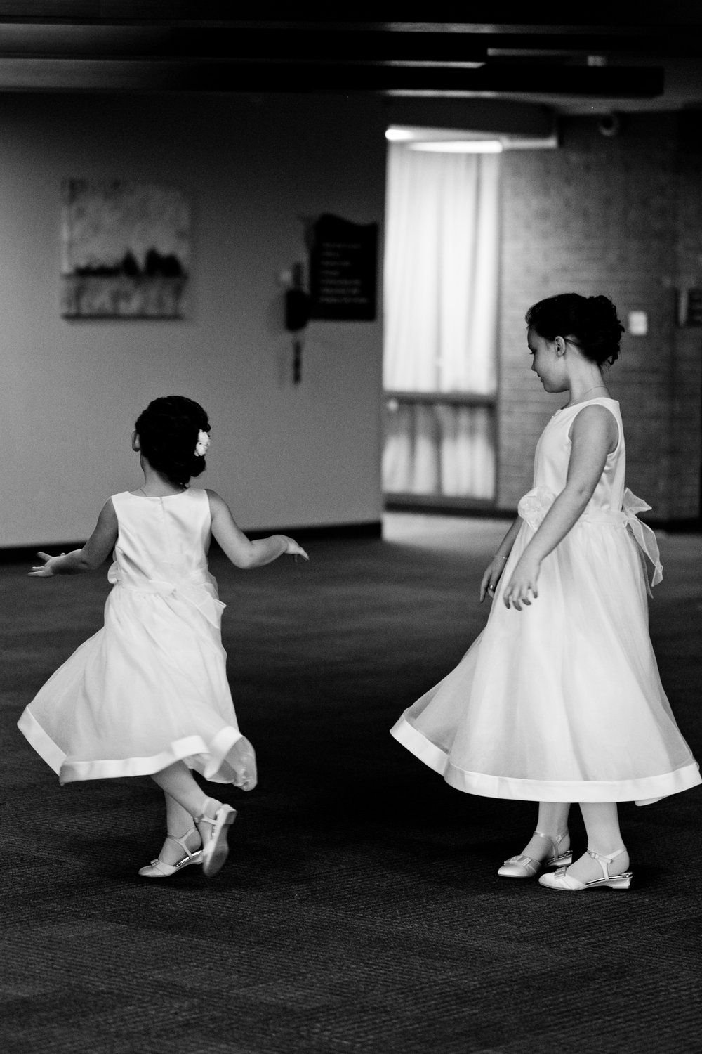 flowergirls twirling in dresses candid photography des Moines cedar falls iowa wedding