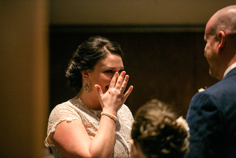 bride wiping away tears during wedding ceremony emotional intimate weddings