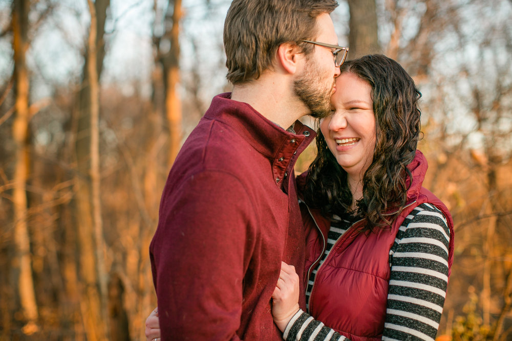 cute couple kissing in front of fall trees in ankeny des moines park engagement photos