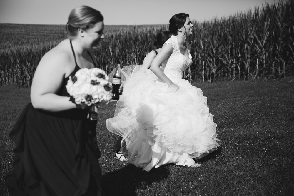 bride running up hill with bridesmaids