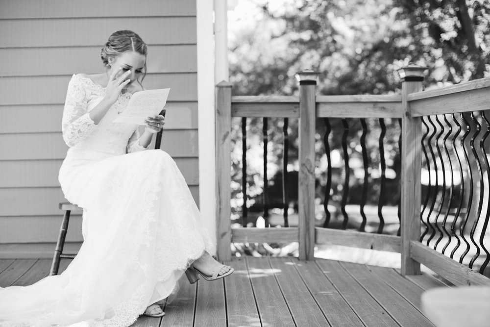 bride reading letter from fiance on her porch morning of wedding