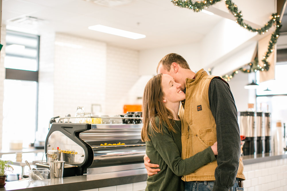 couple kissing in coffee shop engagement photos under christmas lights