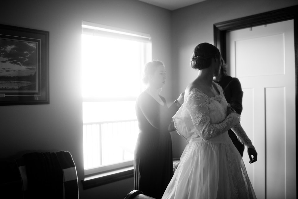 bride putting on her wedding dress in her parent's cedar rapids home