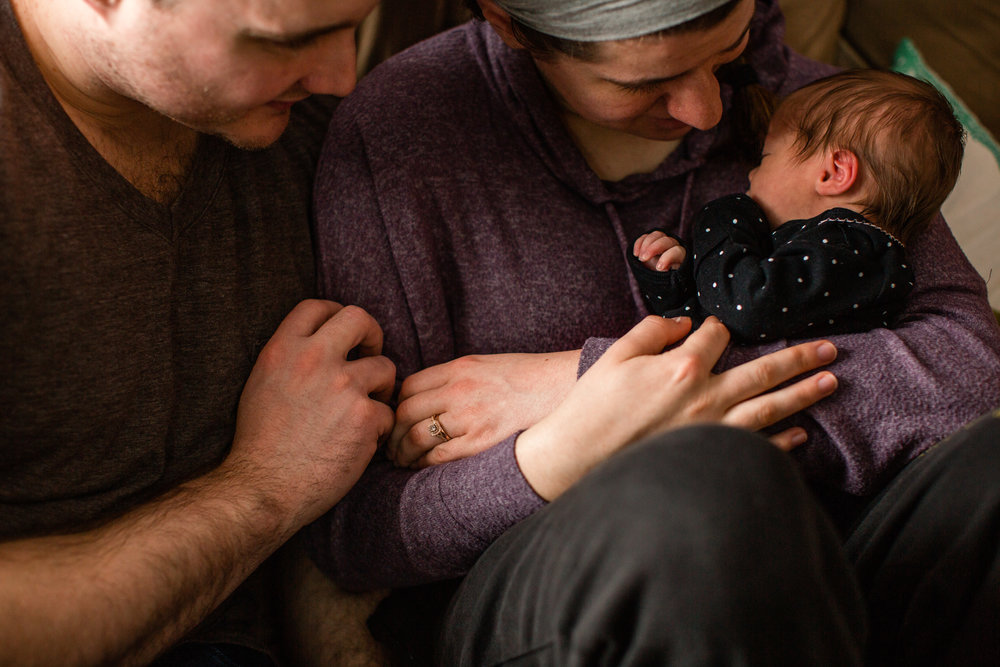parents holding 5 day old baby newborn at home