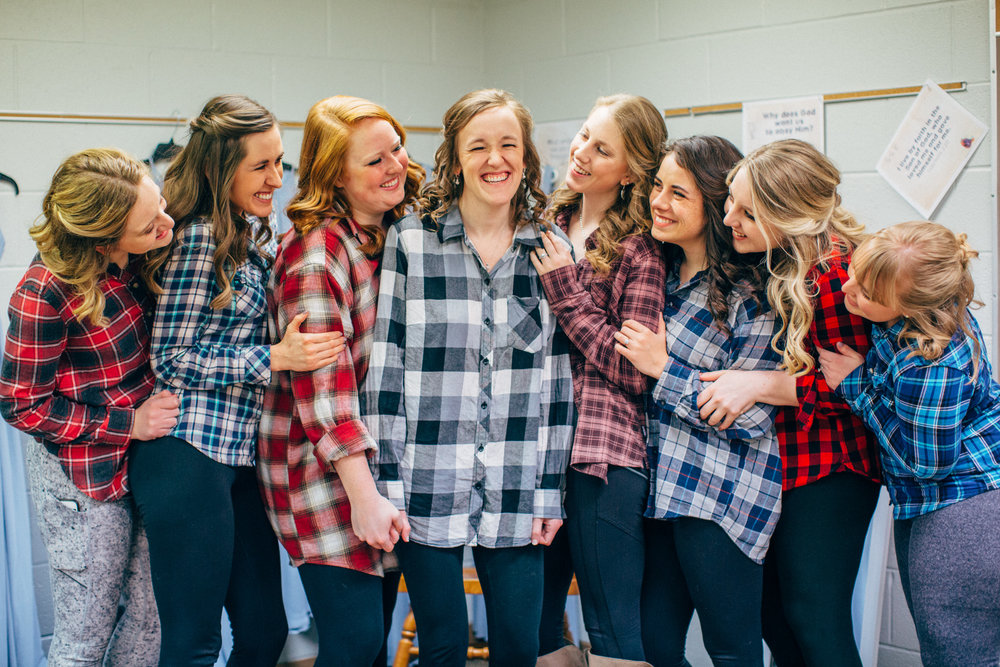 bride and bridesmaids laughing together before getting dressed wearing flannel shirts