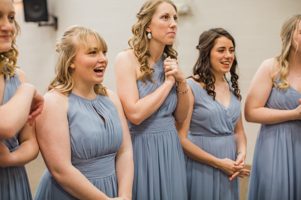 sister in law and bridesmaids seeing bride kristen for first time in dusty blue dresses