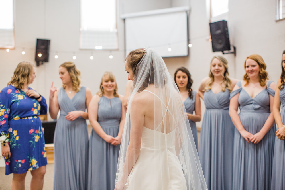 first look with bridesmaids inside church winter wedding ideas