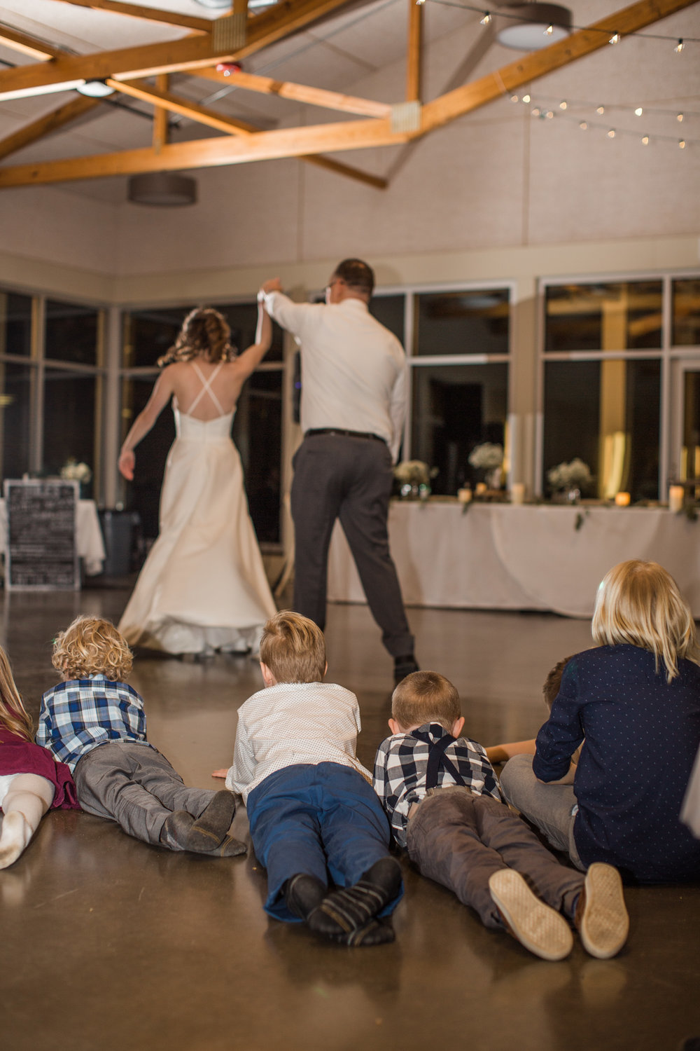 kids watching bride dance with her dad at wedding reception