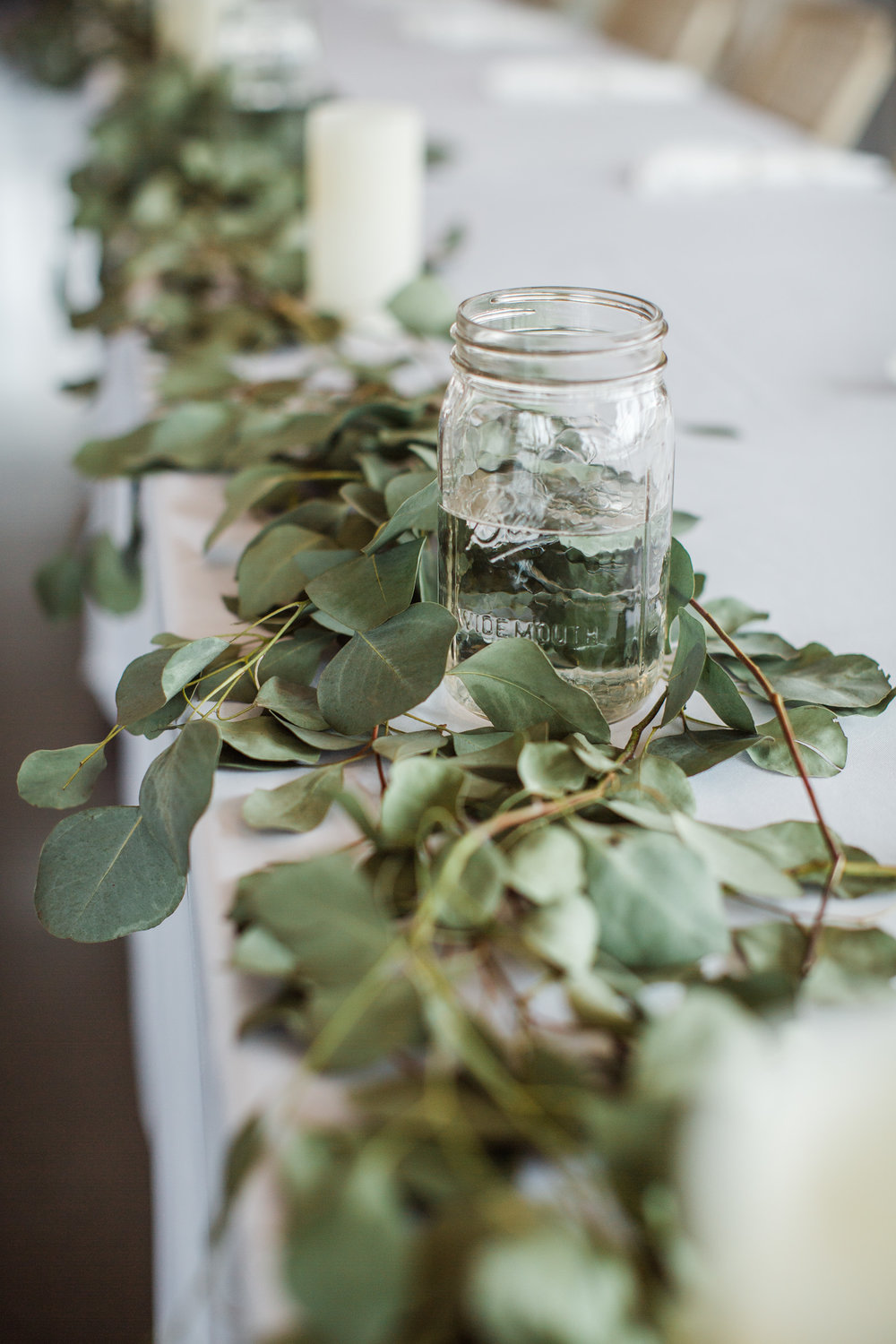 mason jars and eucalyptus on head table wedding reception