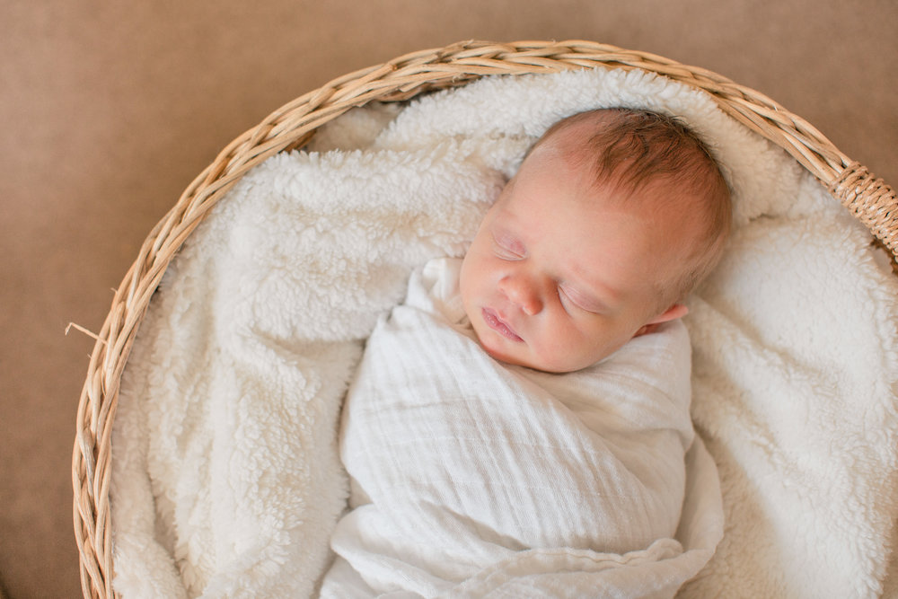 sweet newborn girl sleeping in swaddle inside basket with white blanket